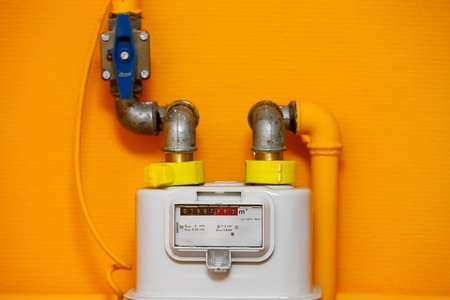 Gas meter on orange wall Stock Photo