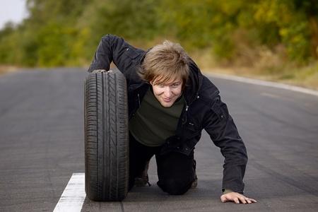 arrodillarse: Hombre que sostiene una rueda en la carretera Foto de archivo