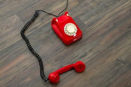 hangup: Red vintage phone on the floor