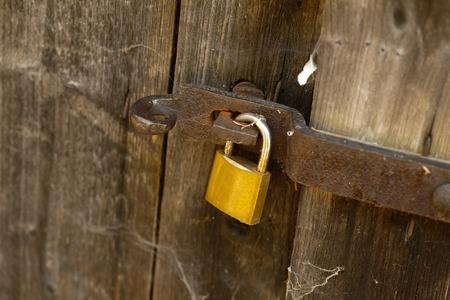 Padlock on an old wooden barn door photo