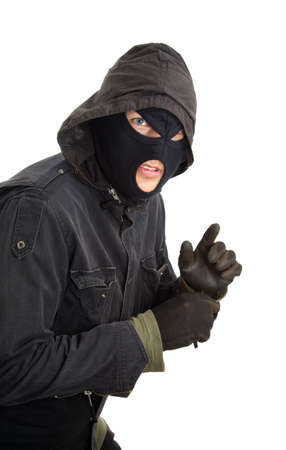 disguised: Robber in a black mask sneaking inside Stock Photo