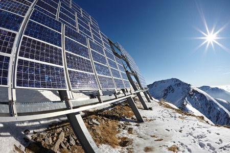 Big cluster of solar panels on a mountain peak photo