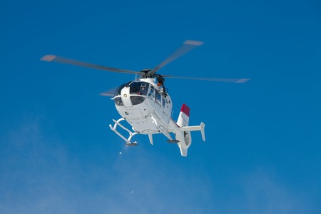 skiing accident: Mountain rescue helicopter against clear blue sky