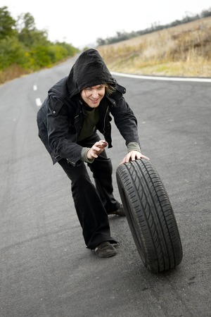 Man holding a wheel on the road photo