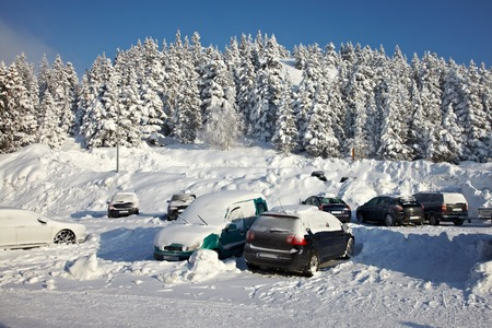 snow covered mountain: Parking cars covered by a lot of snow