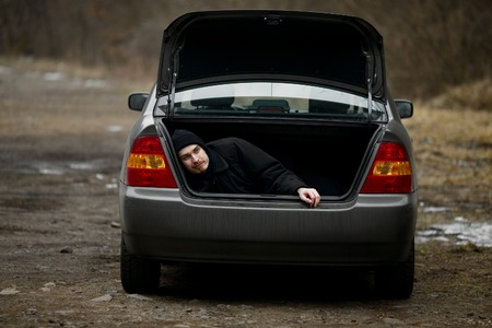 abduct: Man in the trunk of a car Stock Photo