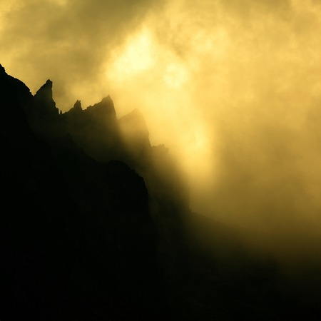 dramatically: Clouds dramatically glowing over a mountain ridge