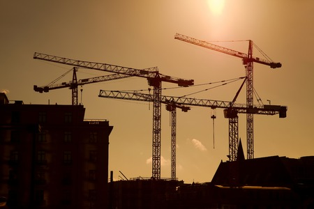 Tower crane silhouettes at a construction site photo