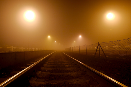 Rails in the fog at night photo