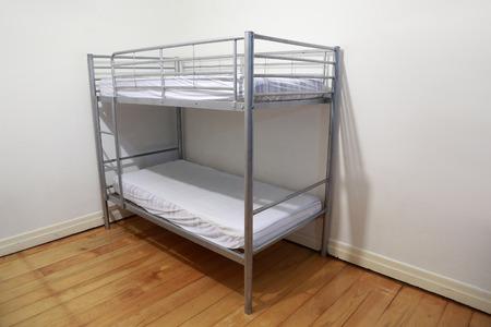 literas: Cama litera simple en la esquina de una habitación
