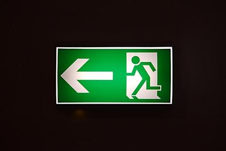 salida de emergencia: Señal de salida de emergencia brillando en la oscuridad