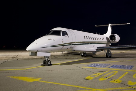 Small jet plane parked at night