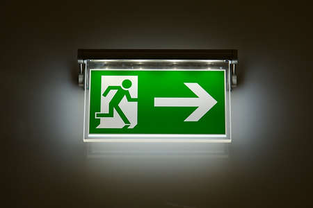 fire escape: Emergency exit sign glowing in the dark