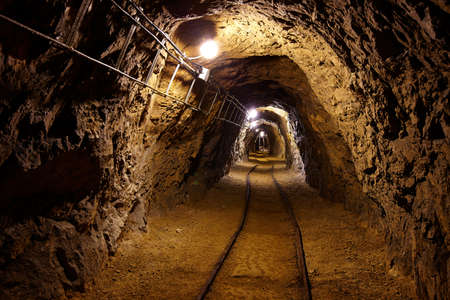 Mining tunnel with lights and rails photo