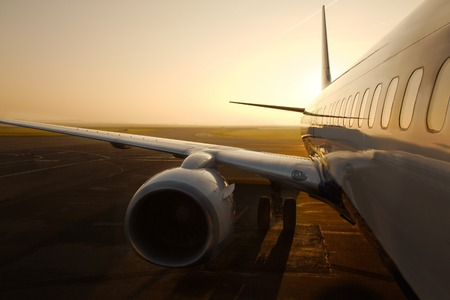 industry park: Airplane at an airport at sunrise Stock Photo