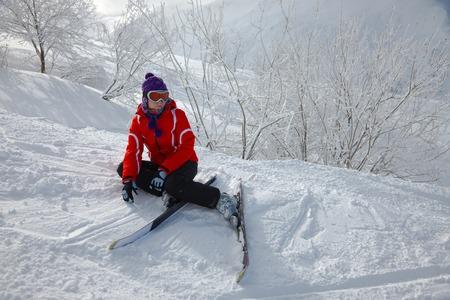 Female skier fallen in deep snow photo