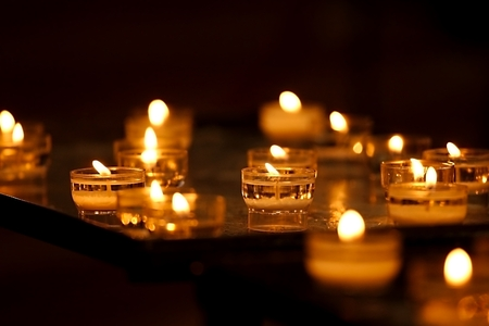 prayer candles: Rows of burning candles in a dim church Stock Photo