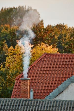 incendio casa: Chimenea en un techo de una casa