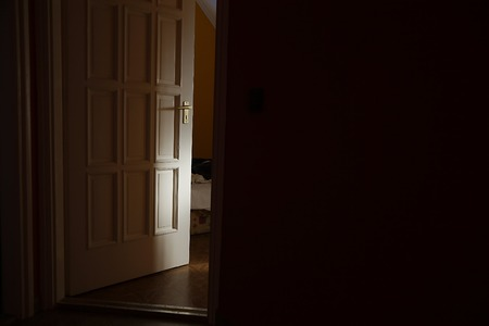 Light coming from a room with door left ajar Stock Photo