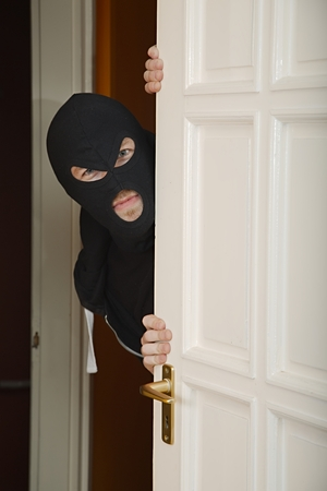 trespasser: Robber in a black mask sneaking inside Stock Photo