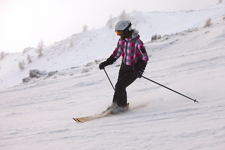 Female skier coming down the slope photo