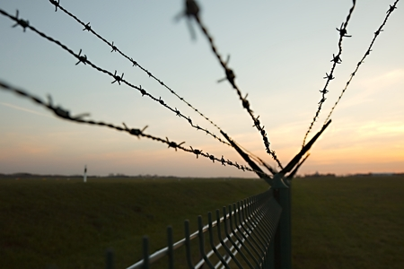 intrude: Barbed wire fence against clear blue sky
