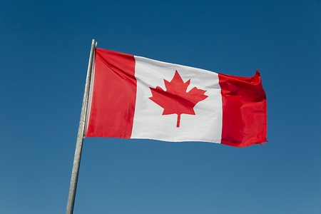 canadian flag: Canadian flag waving against blue sky