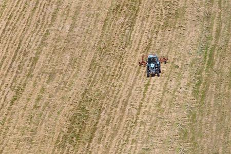 arando: Tractor arando el fild. Marcas eliminado, esquema de color original cambiaron Foto de archivo