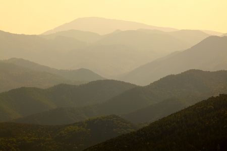 distant: High mountain landscape in hazy weather, soft natural background.