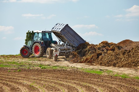 plough machine: Old tractor dumping manure from a trailer. Vehicle colors changed. Stock Photo
