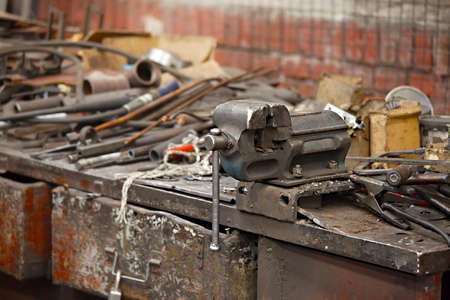 greasy: Messy workshop table with vise and old tools Stock Photo
