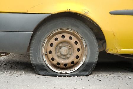 decadence: Flat tire of an old car Stock Photo