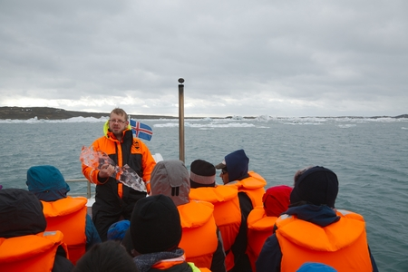 tour guide: JOKULSARLON, ICELND - MAY 10, 2015: Tour guide talking about the the icebergs on an amphibian tour on the glacier lake Jokulsarlon, Iceland Editorial