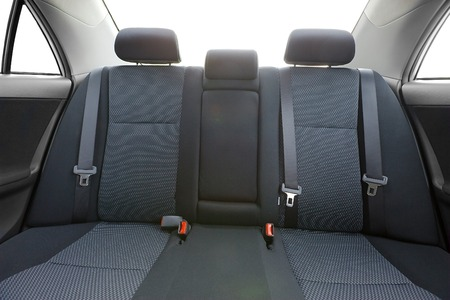 headrest: Car interior with back seats, sunlight flaring through