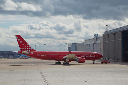 kastrup: COPENHAGEN, DENMARK - MAY 13: Air Greenland A330 towed into hangar at Kastrup Airport, May 13th 2015. This Airbus A330 is the largest airliner of Air Greenland.