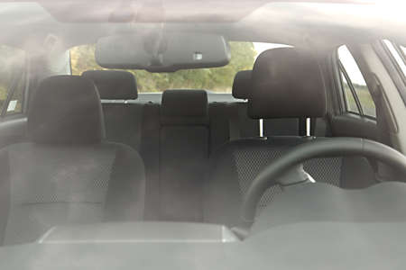 back seat: Car interior behind flaring reflections of the windscreen Stock Photo