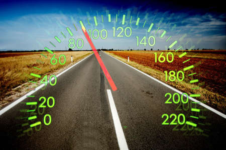 Speedometer over empty road landscape