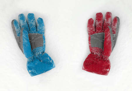 seasonic: Blue and red gloves lieing on the snow Stock Photo