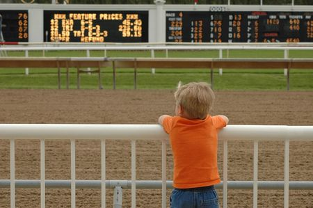 race track: Young boy deep in thought at race track