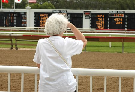 race track: Elderly woman at horse race track