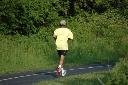 lonelyness: Man in yellow shirt jogging Stock Photo