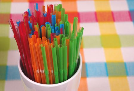 Vibrant colored straws in white glass on colorful mat