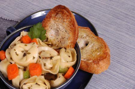 tortellini: Warming bowl of tortellini soup with crostini Stock Photo