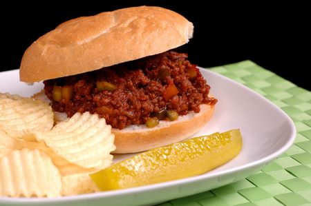 sloppy: Sloppy Joe sandwich with chips and pickle on a white plate and bright green mat