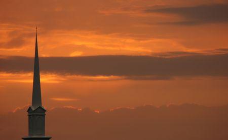 church steeple: Lo steeple della chiesa si � regolato contro un tramonto dorato drammatico Archivio Fotografico