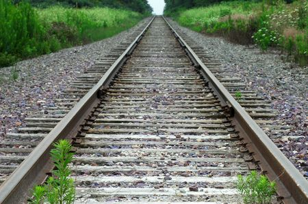 lonelyness: View along deserted railroad tracks with green foliage
