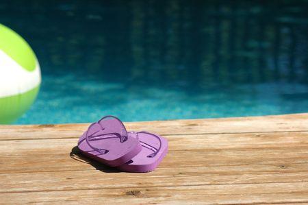 Purple sandles on a deck poolside photo