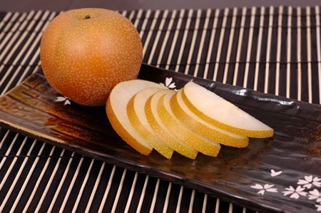 asian pear: Asian pear whole and sliced on oriental plate Stock Photo