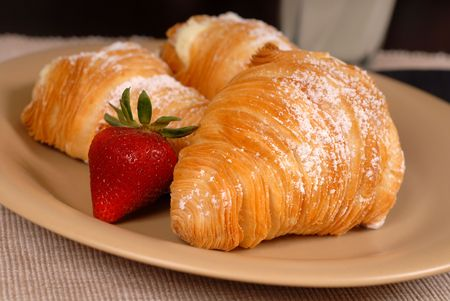 rich flavor: Three sfogliatelles with strawberry on tan plate Stock Photo