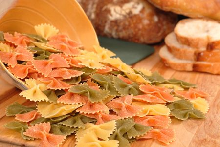Uncooked tri-colored farfalle pasta spilling out of bowl onto cutting board with italian bread photo